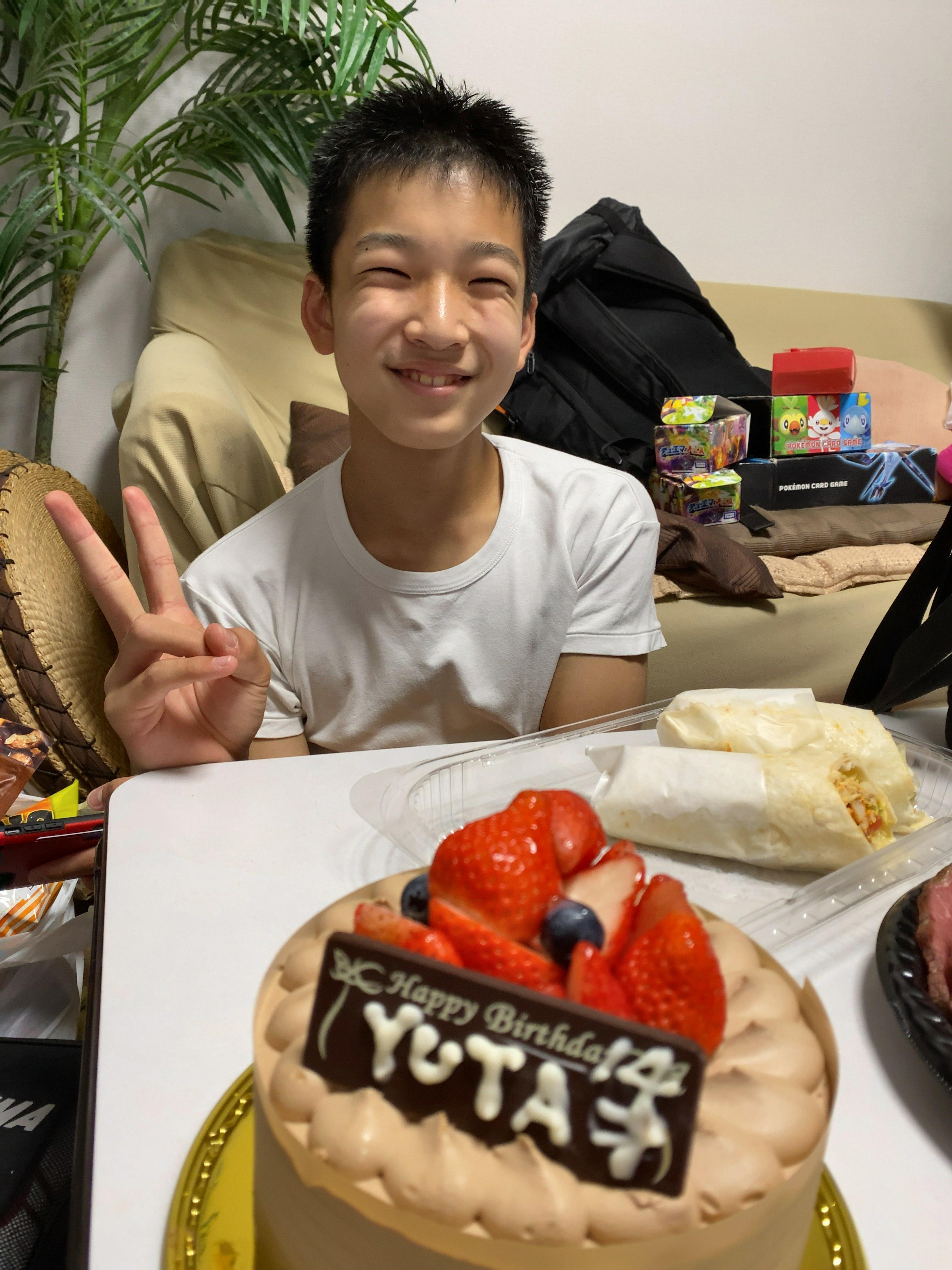 誕生日ケーキとピースをする子供